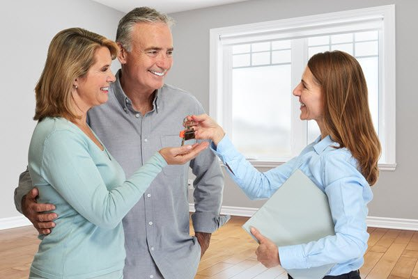 real estate agent giving house keys to couple